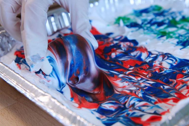 Надеваем перчатки. Берем яйцо и окунаем его в цветную пену, покрываем равномерно со всех сторон.
